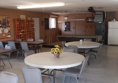 A photograph of the common area at Goldwater Estates RV Park. White chairs and tables are in the foreground with mailboxes and a kitchen area in the background.