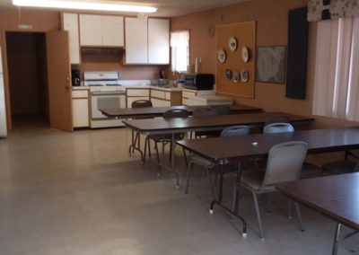 A photograph of the common area at Goldwater Estates RV Park. White chairs and tables are in the foreground with a kitchen area in the background.
