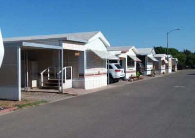 A photograph of RV sites at Goldwater Estates RV park. There are some RV homes in the background. The photo was taken on a bright and sunny day with clear blue skies.